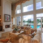 bright Florida living room, high ceilings, tall windows, view of turquoise swimming pool