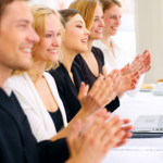 Photograph of a business team applauding.