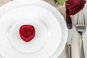 small heart shaped velvet box on white dinner plates