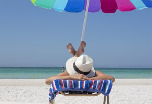 woman lying on a chaise on the beach, white sand and turquoise Florida water, colorful umbrella