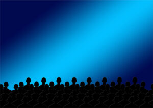 black silhouettes of heads of people seated in a theater blue light shining across the background